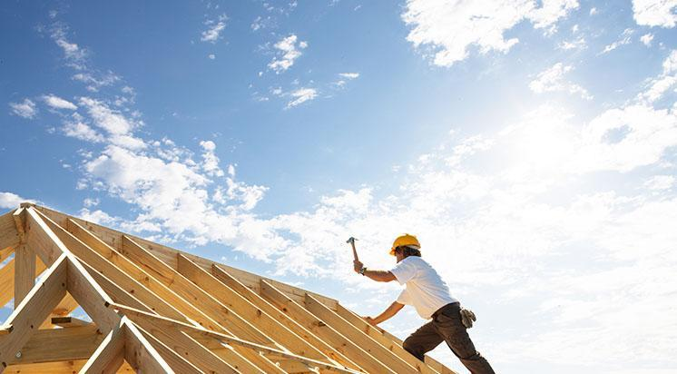 Mężczyzna montujący więźbę dachową